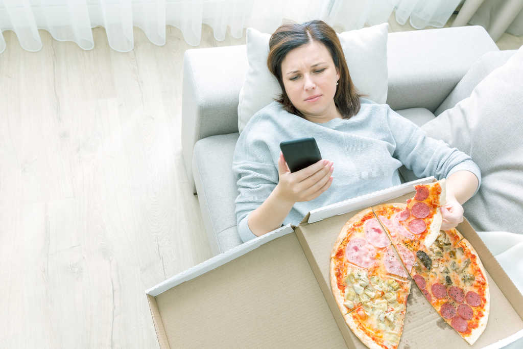 woman stress eating pizza